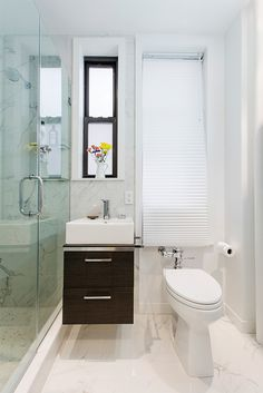 Upper West Side bathroom renovation features a minimal-footprint floating vanity in a dark wood finish with two drawers for storage, supporting a white porcelain basin, adding a touch of drama to the neutral decor, and a narrow, tank-less toilet with a traditional lever.