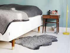 Amusing White Fabric Queen Size Bed With Brown Wooden Legs features Grey Fur Rug and Brown Varnished Wooden Nightstand