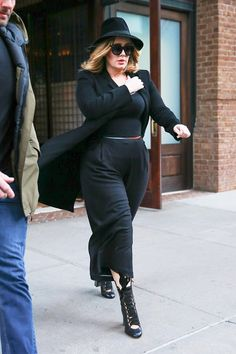 Adele wears a belted black jumpsuit, long blazer, fedora, and lace-up Chloé boots