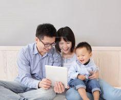 Una familia feliz, madre, padre, hijo sentado en la cama en su casa teniendo diversión con un pc tablet PC, gente asiática Foto de archivo