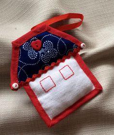 Modrotiskový domeček Šitá ozdobička ve tvaru domečku z modrotisku a bílé bavlněné látky ozdobena knoflíčky červené a bílé barvy od Postaráme se a červeným stehem. Střecha vyplněna vatelínem. Červená stužka k zavěšení. Velikost ozdobičky 8 cm.