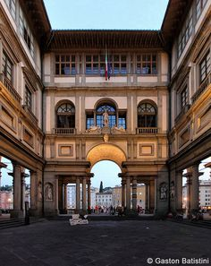"""The Uffizi Gallery--Building of the palace was begun by Giorgio Vasari in 1560 for Cosimo I de' Medici as the offices for the Florentine magistrates — hence the name """"uffizi"""" (""""offices""""), continued to Vasari's design by Alfonso Parigi/Bernardo Buontalenti 1581. The cortile is so long, narrow, open to the Arno River at its far end through a Doric screen that articulates the space without blocking it, that architectural historians treat it as the first regularized streetscape of Europe…"""