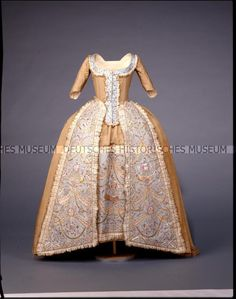 Robe à la francaise, c. 1783. Golden silk, front panels and petticoat embroidered with sequins, coloured silk and metal threads on pale blue silk ground.