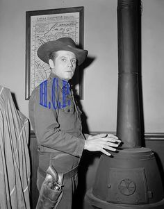 JACK LORD IN A WESTERN COSTUME, WARMING HIS HANS OVER A STOVE ON THE SET B&W PIC