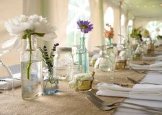 keep your flower budget down by using recycled bottles and jars with single stems to decorate your wedding table