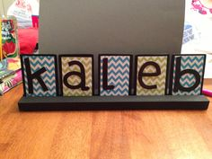 Rectangle wooden craft pieces with mod podged scrapbook paper and pre-colored chipboard letters : )  Sure can't wait to meet the little fella!
