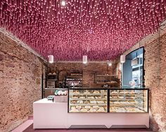 ideo arquitectura adds undulating pink canopy to madrid pastry shop
