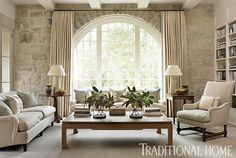 Reclaimed limestone frames a beautiful floor-to-ceiling arch window in this light-filled family room. - Traditional Home ® / Photo: Emily Jenkins Followill / Design: Phoebe Howard
