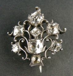 Paste giardinetti brooch, Georgian, circa 1770. Flowers were a fashionable theme in jewellery during the second half of the 18th century. 'giardinetti' items (from the Italian, meaning 'little garden') were popular. They had tiny blossoms set with an assortment of precious stones, asymmetrically arranged in a basket, vase or pot