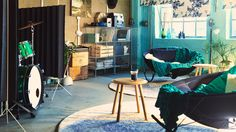 Huone, jossa kaksi modernia keinutuolia, vihreät huovat ja kaksi pyökkistä apupöytää. Taustalla kaksi sinkitystä teräksestä valmistettua säilytyskalustetta täynnä musiikkilehtiä ja vanhoja levyjä.
