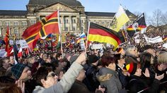 Supporters of Pegida hold flags during a demonstration at Konigsufer Square in Dresden, Germany on February 6, 2016.