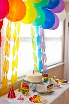 Baloons in rainbow colors and twisted paper in pastel colrs like a centrepiece in the wall
