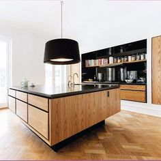A variation over one of our classic designs - Model Minimal. A large island with drawers on all four sides. #bespokekitchen #madetomeasure #blackgranite #americanelm #tallcabinets #cookingniche #oakherringbone #blændendeboliger