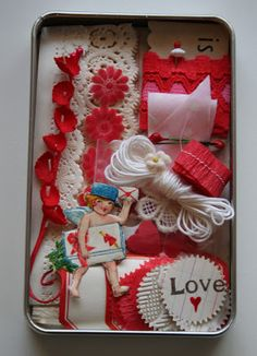 "contents: cupid the postman, two sizes of german paper lace, vintage ledger paper that folds into a tiny envelope, dennison red bordered labels sizes 201 & 205, vintage string, a length of pink polka dot bias trim, red & pink lace wound around a vintage playing card, spray of red lily of the valley, tiny pink flocked daisies, several red velvet hearts and a cream applique, hand sewn crepe paper ruffle 1/2"" wide, several seals punched from vintage wallpaper, ledger paper, crepe paper"