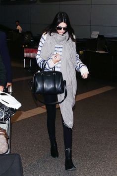 Kendall Jenner's airport style: black jeans, booties, striped sweater, and bulky scarf. Black Givenchy bag to top it off.