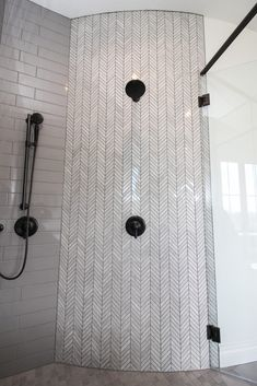 Gray master shower and tub surround with white chevron accent tile. Glass shower door with black finishes.
