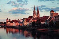 "Regensburg Old Town The view from the bridge ""Eiserner Steg"" towards the Danube riverbank and the picturesque old town dominated by St. Peter Cathedral. Jonas Lang-Youronas flickr"