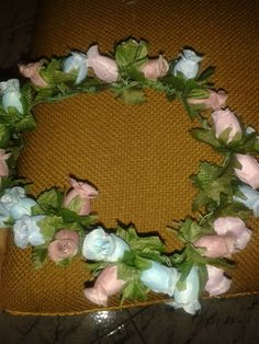 Corona de flores de tela en tonos pastel.