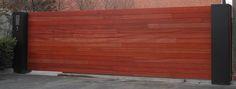 Geautomatiseerde opritpoort in padouk met symmetrische consoles in zwarte structuurlak en geïntegreerde videofonie! #wood #bois #oogvoordetail #duurzaam #tijdloos #automatic #garden #driveway #gate #portail #automatic Meer info: www.emts.be