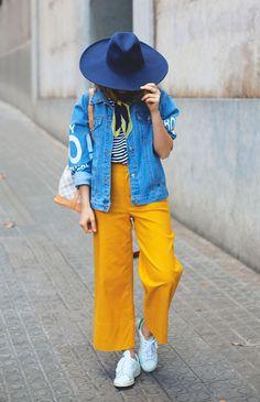 Street style look jaqueta jeans, blusa listrada, calça amarela e tênis branco.