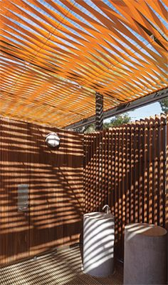 The pavilions are roofed with woven strips of orange webbing, which cast vibrating shadows. Image: Brett Boardman