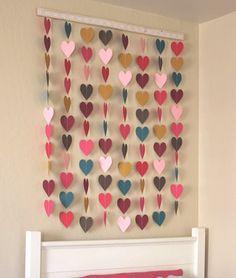 cortina-de-coracoes-4 Materiais  - Base de madeira para suspender a cortina de corações - Cartolinas de várias cores - Linha - Máquina de costura - Molde de coração impresso - Fita ou renda para colar na base de madeira (opcional)