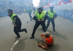 Boston Marathon Bombing - 2013 - Police officers react immediately after an explosion near the finish line of the Boston Marathon.