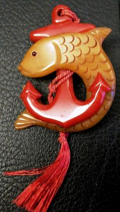 "Vintage 1930s 40s Bakelite Anchor and Fish brooch pin - measures 2-3/4"" by 2-1/2"" (not including the fabric tassel) - the fish and the anchor are two separate pieces of Bakelite that are riveted together and with inset pin mechanism at back."