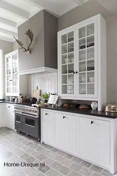 White Kitchen with big glass cabinets. Muted wall colors with accents and great tile floors.