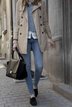 White shirt under grey sweater, beige trench coat, blue skinny jeans, black loafers.