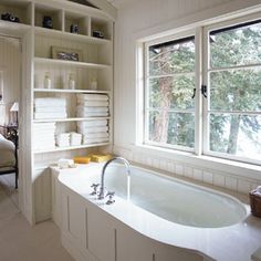 Placed under windows in a second-story bathroom, this undermount tub with smooth stone surround and wood-paneled sides offers excellent views of the treetops. The center-mounted faucet allows two bathers to sit comfortably.