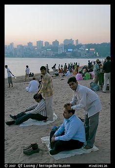 Head masseurs and Mumbai skyline at sunset,  Chowpatty Beach. Mumbai, Maharashtra, India (color)