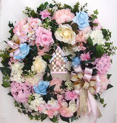 "This beautiful Spring, Summer Ribbon flower door wreath sets on a nature grapevine wreath base. The wreath is embellished with lots of greenery, beautiful pink/white Hydrangea, white Hydrangea, pink/white Roses, light blue Roses, and pink Carnations. The wreath is accented with a hand painted beige and white Parchment check Bird House. I finish the wreath with two beige/white/pink ribbon bows. 27"" (L) x 26"" (W) x 7.5""(D)."