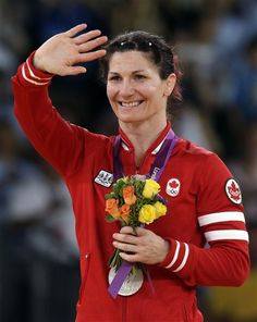 Silver medalist Tonya Lynn Verbeek of Canada smiles with her medal during the victory ceremony for the 55-kg women's freestyle wrestling competition at the 2012 Summer Olympics, Thursday, Aug. 9, 2012, in London.