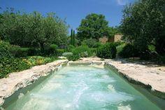 <p>Installée dans un jardin provençal, cette piscine spa possède un aspect très naturel, accentué par un fond couleur sable en Crystalroc. Elle est équip...