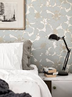 Stadshem bedroom vintage large flowery wallpaper washed linen sheets white and grey chunky knit throw black desk lamp