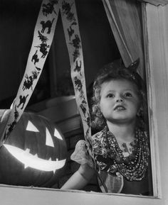 A little girl waiting at a window for the first guests to arrive at her Halloween party, 1955. #vintage #1950s #Halloween