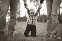 a cute baby boy holding mommy and daddy's hands . Cute 6 month photo idea