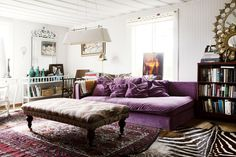 Living Room Photo - A purple couch and layered rugs in a living space