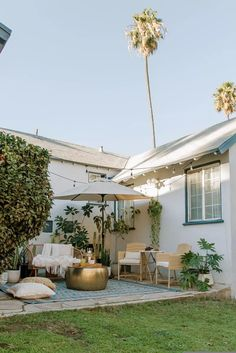 A yard filled with plants, furniture, and outdoor string lights