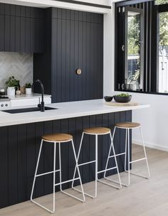 "The dark kitchen cabinetry is a nod to the exterior, ""as the pattern of the shiplapped cladding informed the grooves of the kitchen joinery,"" says the firm. Kitchen Pleated House by Megowan Architectural"