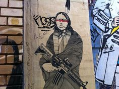 Wheat-paste street art poster of Native American in traditional garb and toting a modern, high-powered assault gun near the corner of Wooster and Grand streets in SoHo, in downtown Manhattan, NYC.