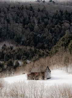 Small brown country barn nestled in the snowy elbow of a series of rolling hills.