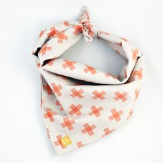 """This simple grey with bright orange cross bandana is the perfect pop of colour for spring! * Cotton printed fabric * Classic size is a 18"""" square and measures 24"""" across * Small size is a 13"""" square a"""