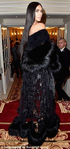 Dramatic: Kim paired her top and leggings with a dramatic floor length fur coat as she posed for pictures at the bash