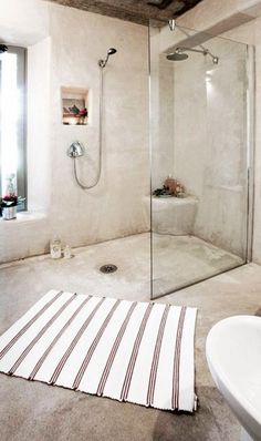 Neutral, polished concrete extending throughout the bathroom makes this a beautifully streamlined sight.