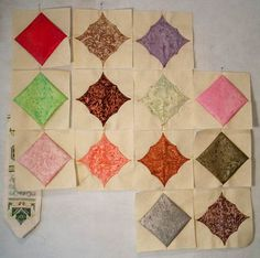 10-Minute Blocks with an extra swoop. Love the jewel tones palatte with the ivory background. The cathedral windows are tacked with a pin in the center on each side of the window, forming a double swoop when the bias edge is folded back. Beautiful!