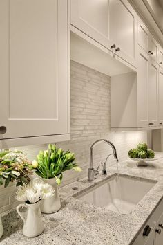 Lovely creamy white kitchen design with shaker kitchen cabinets painted Benjamin Moore White Dove, Kashmir White Granite counter tops, polished nickel modern faucet and Vetro Neutra Listello Sfalsato Glass Mosaic- Bianco tiles backsplash. Benjamin Moore W Kitchen Backsplash Designs, Painting Kitchen Cabinets, Dream Kitchen, Kitchen Colors, Off White Paint Colors, Kitchen Renovation, Backsplash Designs, White Kitchen Design, Kitchen Paint