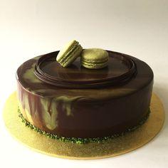 Matcha sponge cake layered with matcha mousse and chocolate/matcha marbling mirror glaze. Decorated with matcha macarons.