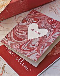 The dreamy curves of marbleizing lend themselves to a number of decorative paper crafts, such as this Valentine's Day card with a heart cut-out. First, learn how to make marbleized cards. After you marbleize the paper and let it dry, cut a piece of white card stock 3 1/2-by-8 inches. Fold in half, scoring with a bone folder. Cut a piece of your marbleized paper to 3 1/2-by-4 inches and trace a heart shape on the back side. Use a craft knife to cut out the window. (To make a...